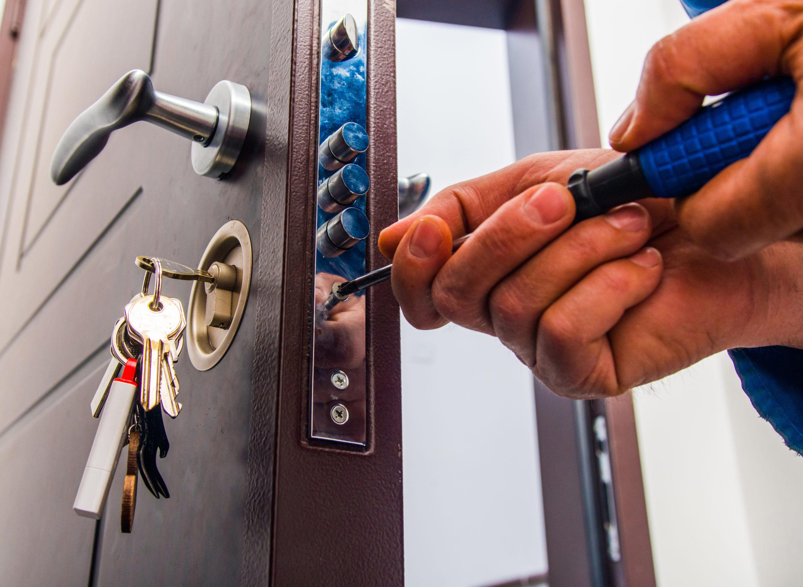 Repairman is standing in the hallway and fixing the door lock with screwdriver